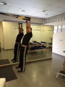 Entrenador de TRX mostrando ejercicios para la Recuperación de hombro mediante ejercicios de TRX.