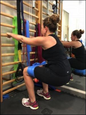 Sentadilla con ayuda para mantener la estabilidad y theraband para activación Glútea. 90º de profundidad y manteniendo rodilla posterior de la punta del pie para mayor fortalecimiento y protección del tendón.